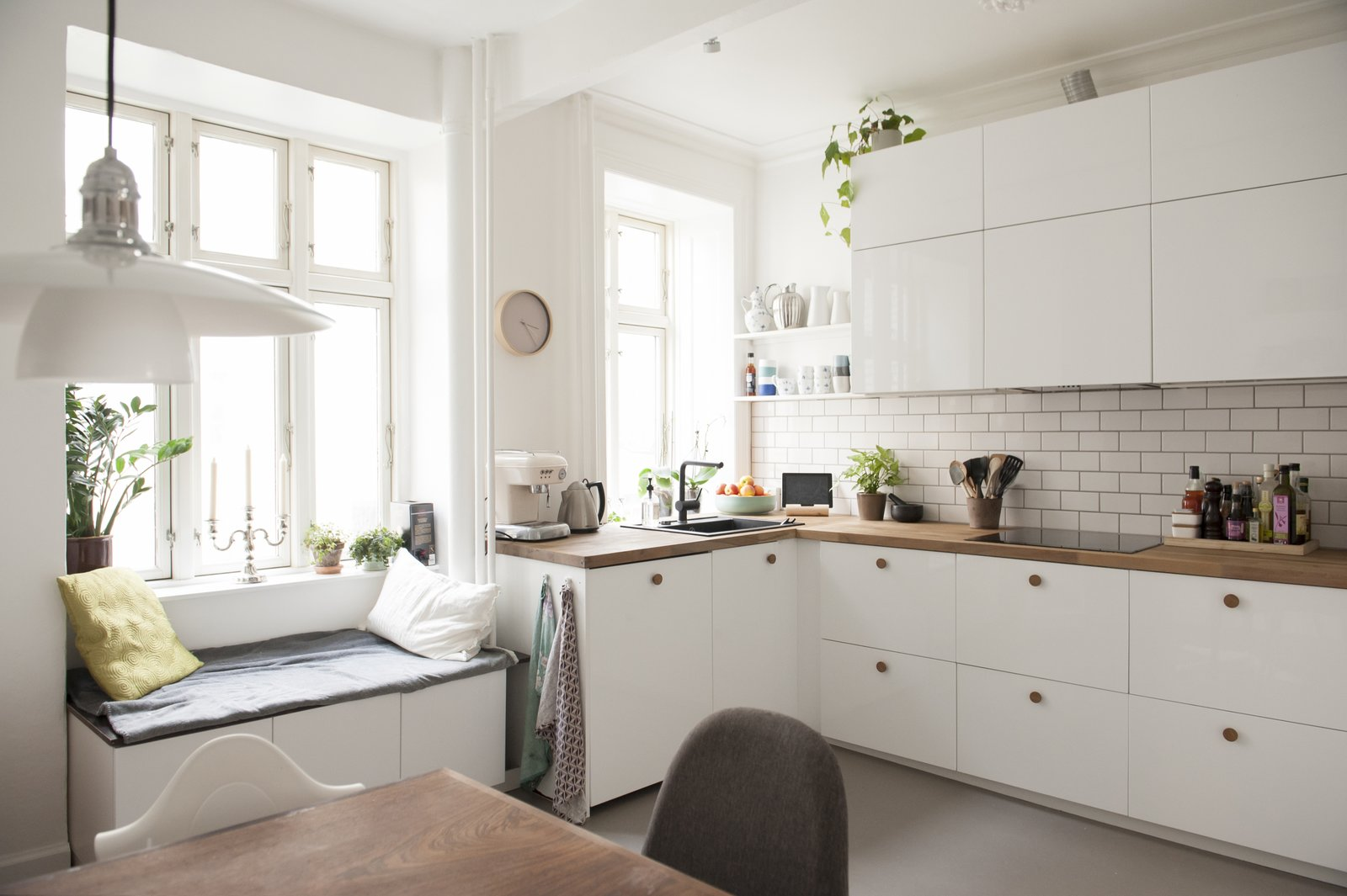 Kitchen, Wood Counter, White Cabinet, Dark Hardwood Floor, Subway Tile Backsplashe, Pendant Lighting, and Drop In Sink white modern kitchen   Pretty and Sweet Family Flat by Petra Ford
