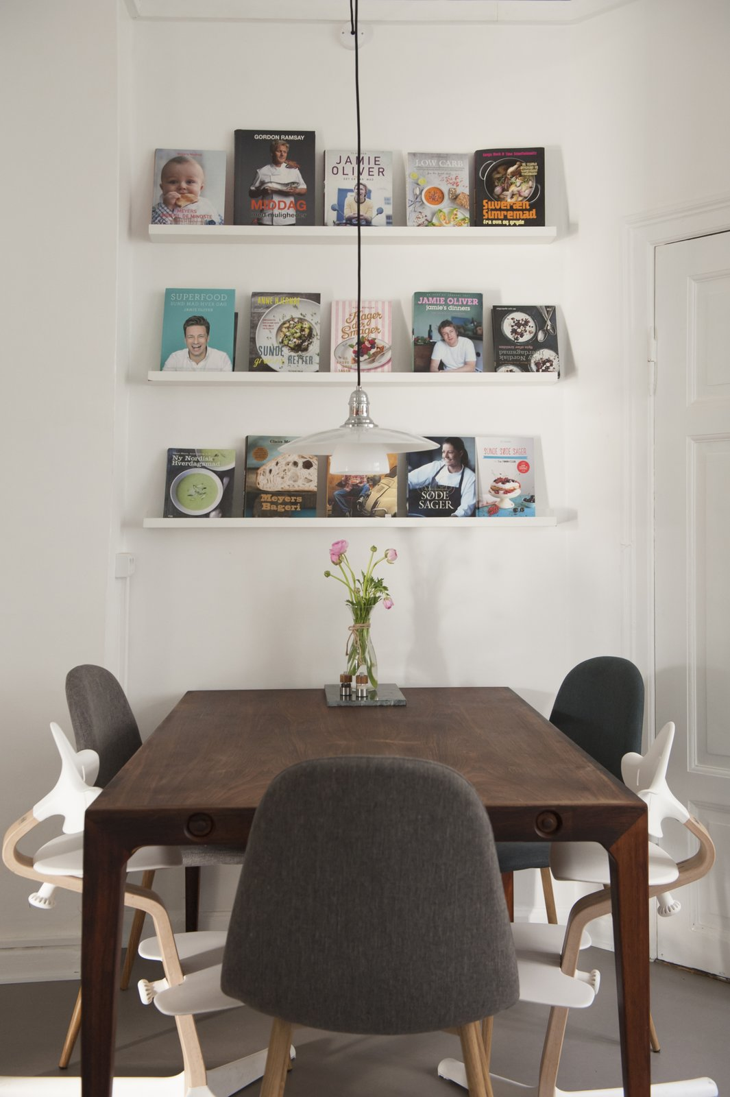Dining Room, Table, Pendant Lighting, and Dark Hardwood Floor kitchen table and book rack filled with cookbooks  Pretty and Sweet Family Flat by Petra Ford