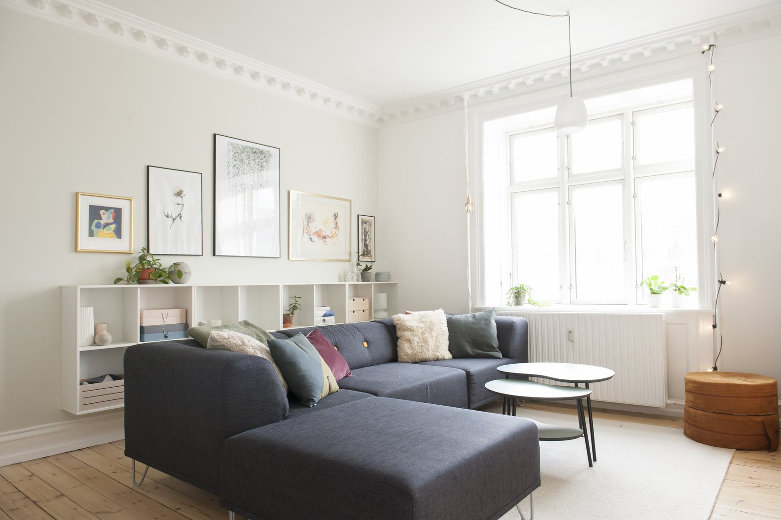 Living Room, Ottomans, Bookcase, Pendant Lighting, Accent Lighting, Coffee Tables, Sectional, Light Hardwood Floor, and Rug Floor living room with navy blue couch, original artwork, and crown molding  Photo 1 of 8 in Read This Before You Hang Up New Artwork from Pretty and Sweet Family Flat