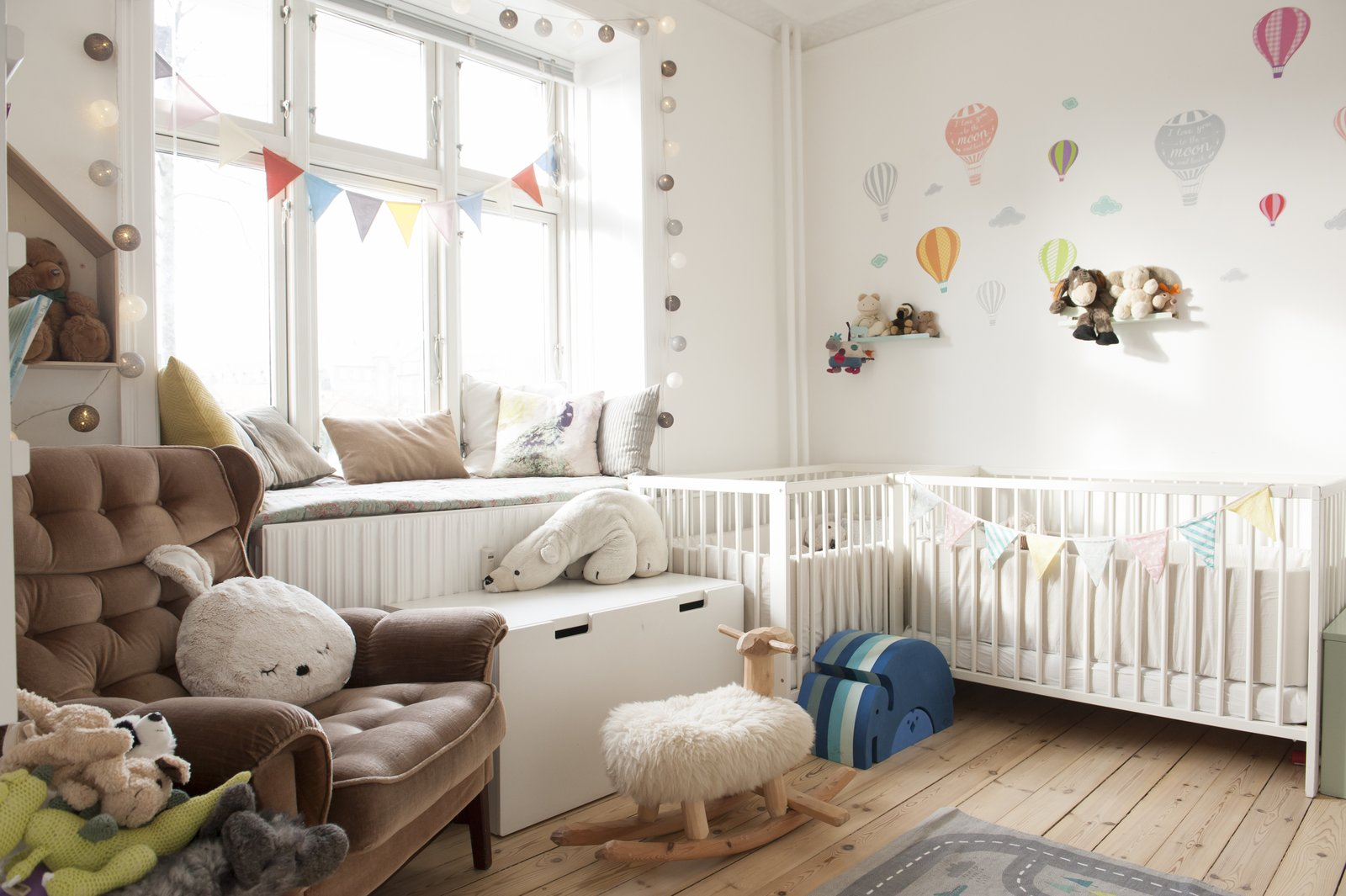 Kids Room, Bedroom Room Type, Bed, Bench, Chair, and Toddler Age children's nursery filled with plush toys, hot air balloon decor, and light strings  Pretty and Sweet Family Flat by Petra Ford