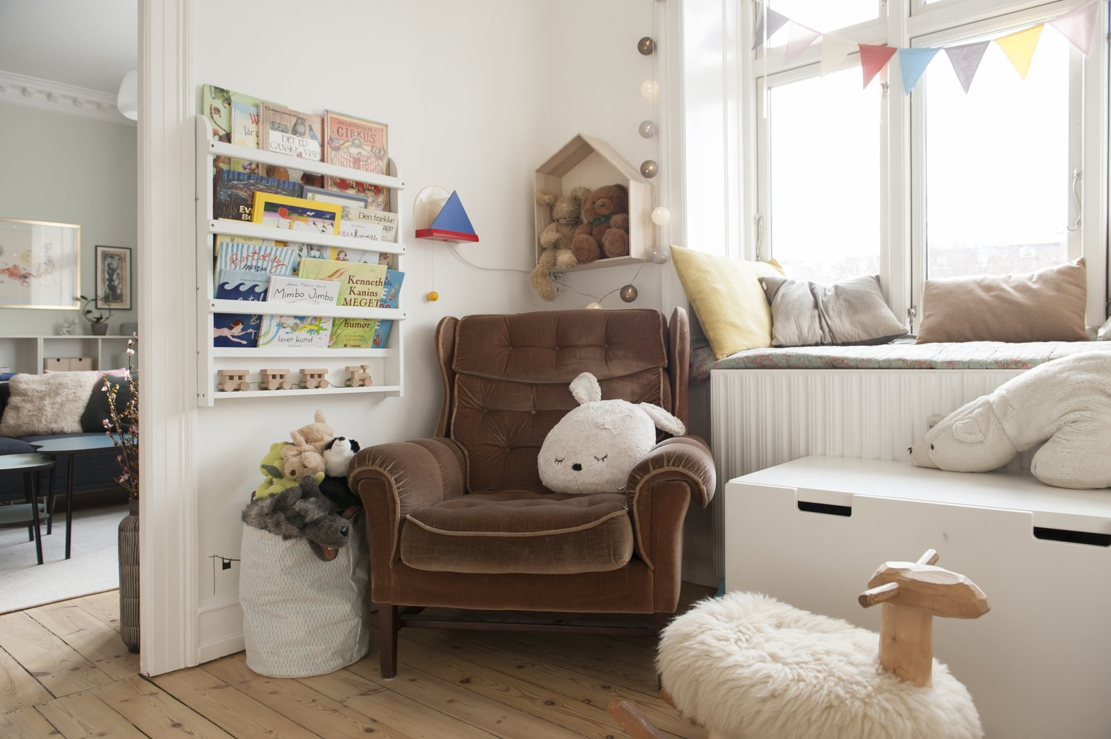 Kids Room, Bedroom Room Type, Chair, Storage, Bookcase, Shelves, and Neutral Gender children's bedroom with brown armchair and books  Pretty and Sweet Family Flat by Petra Ford