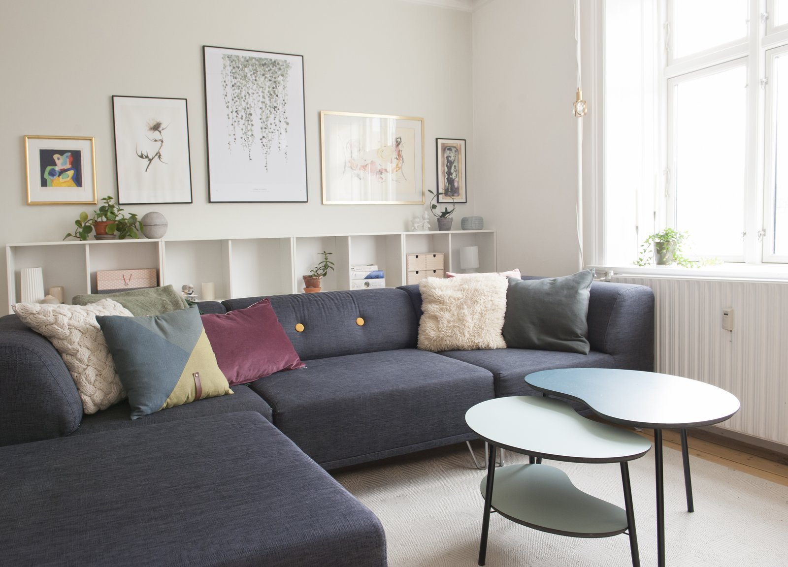 Living Room, Sofa, Bookcase, Sectional, Coffee Tables, and Medium Hardwood Floor contemporary living room with colorful pillows on navy sofa  Pretty and Sweet Family Flat by Petra Ford