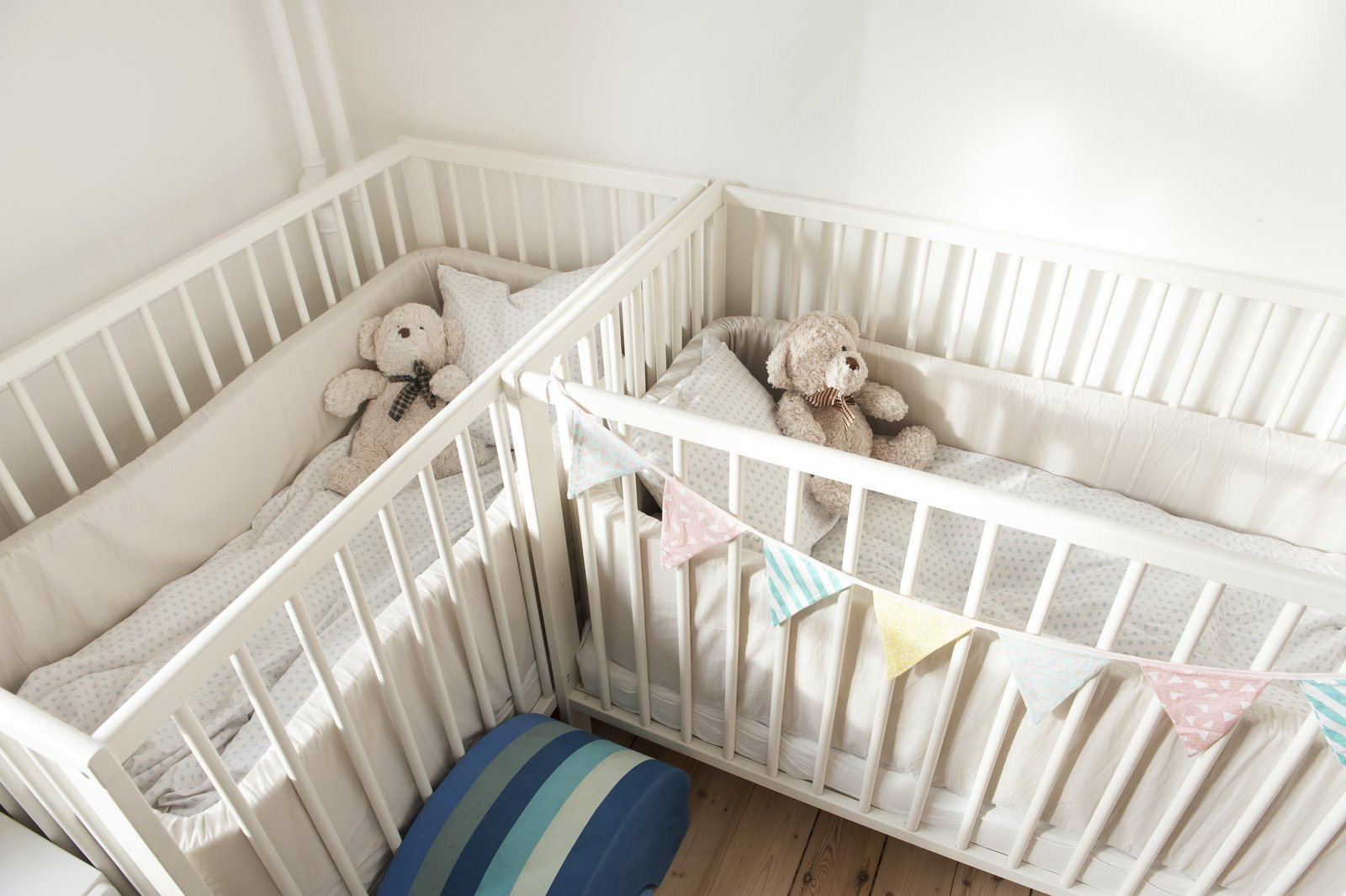 Kids Room, Bedroom Room Type, Bed, Medium Hardwood Floor, Toddler Age, and Neutral Gender cream cribs in child's nursery   Pretty and Sweet Family Flat by Petra Ford