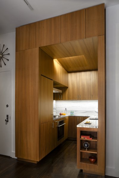 We designed this kitchen like a single piece of teak cabinetry. Lighting and ventilation are recessed into the angled ceiling plane; deep storage is located over the entrance.