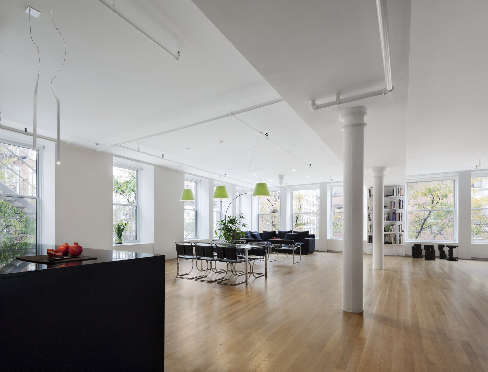 Dining Room, Pendant Lighting, Table, Recessed Lighting, Chair, and Light Hardwood Floor We replaced the windows and concealed the heating units to maximize the distribution of natural light.  Spring Street Loft by Verona Carpenter Architects