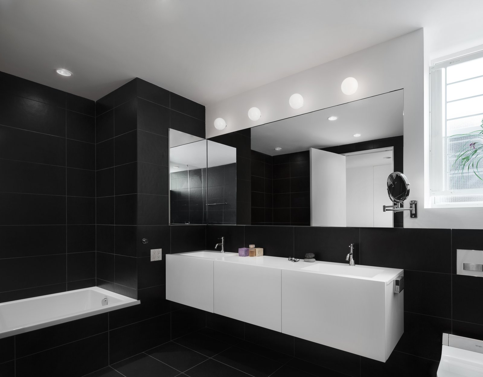 Bath Room and Wall Lighting The bathrooms feature a monochrome aesthetic.   Spring Street Loft by Verona Carpenter Architects