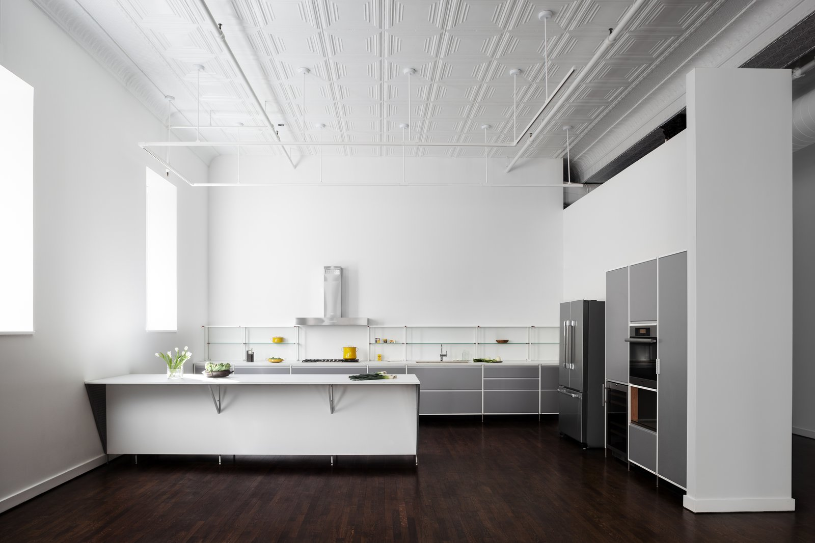 Kitchen, Refrigerator, Cooktops, Range Hood, Dark Hardwood Floor, and Ceiling Lighting We replaced the existing undersized kitchen with a new open plan that is more appropriate to the scale of the loft. Developed with manufacturer Valcucine, the light and industrial feel is in keeping with this unconventional domestic setting.  Broome Street Loft by Verona Carpenter Architects
