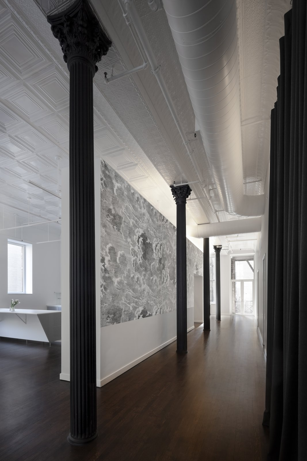 Hallway and Dark Hardwood Floor Along the main hall we installed graphic wallpaper, introducing a new field of texture and tone and transforming the experience of moving between the front and back of the apartment.  Broome Street Loft by Verona Carpenter Architects