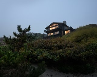 As the house sits atop a cliff on the beachfront, its dwellers can enjoy views of the sandy dunes below.