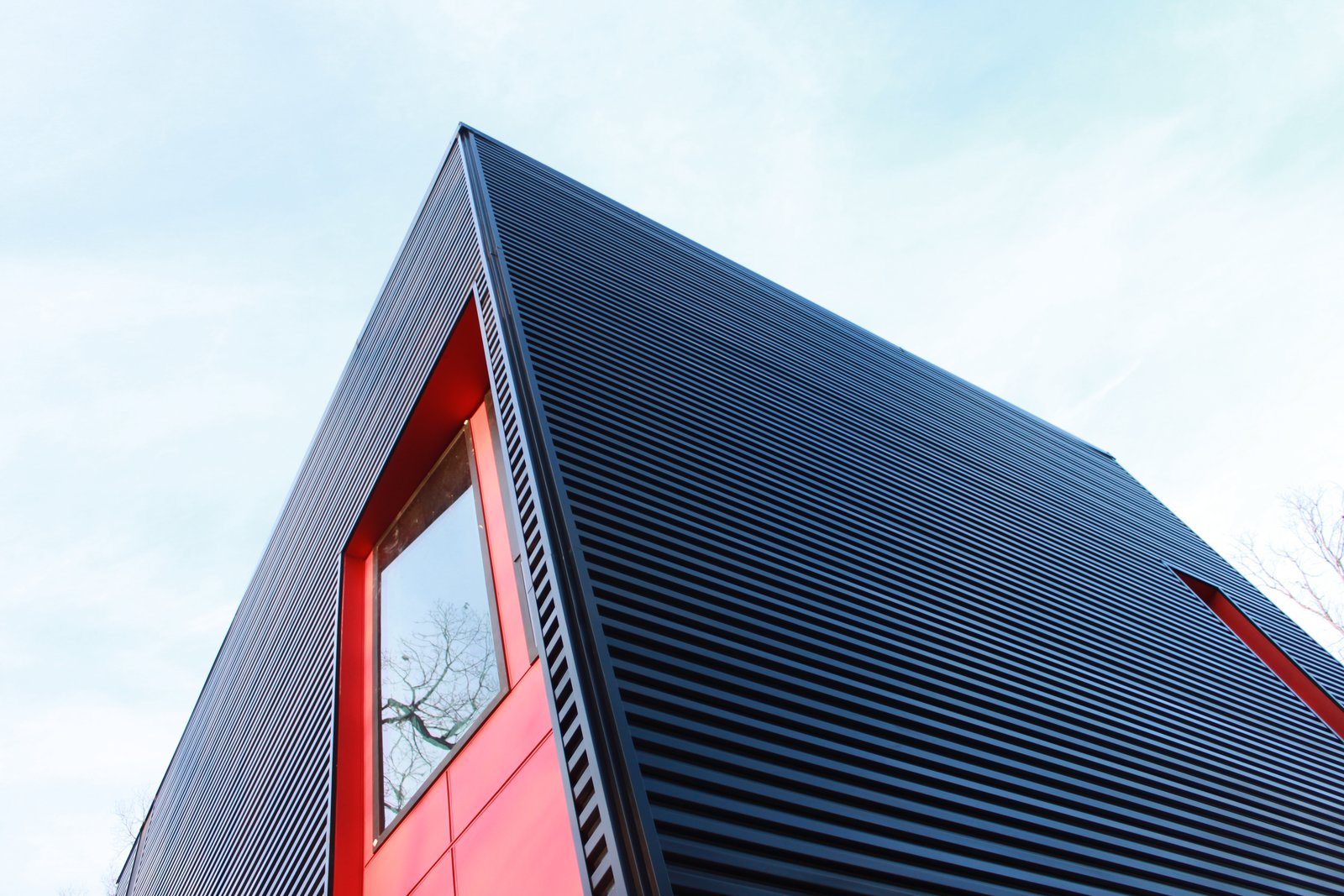 Exterior, Shed RoofLine, House Building Type, Metal Roof Material, and Metal Siding Material The 2-story black metal cube is sliced by red hot gashes.  The Woung House by Toby Witte