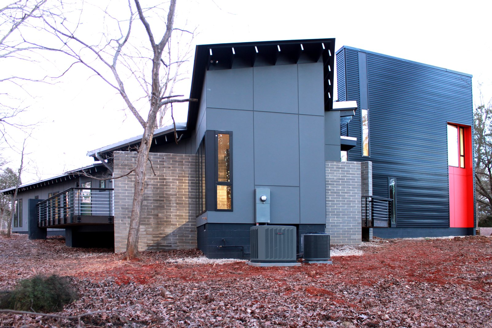 Exterior, Flat RoofLine, Brick Siding Material, Metal Siding Material, Concrete Siding Material, Metal Roof Material, Shed RoofLine, and House Building Type Masonry walls slice through the home and structure the spaces.  The Woung House by Toby Witte