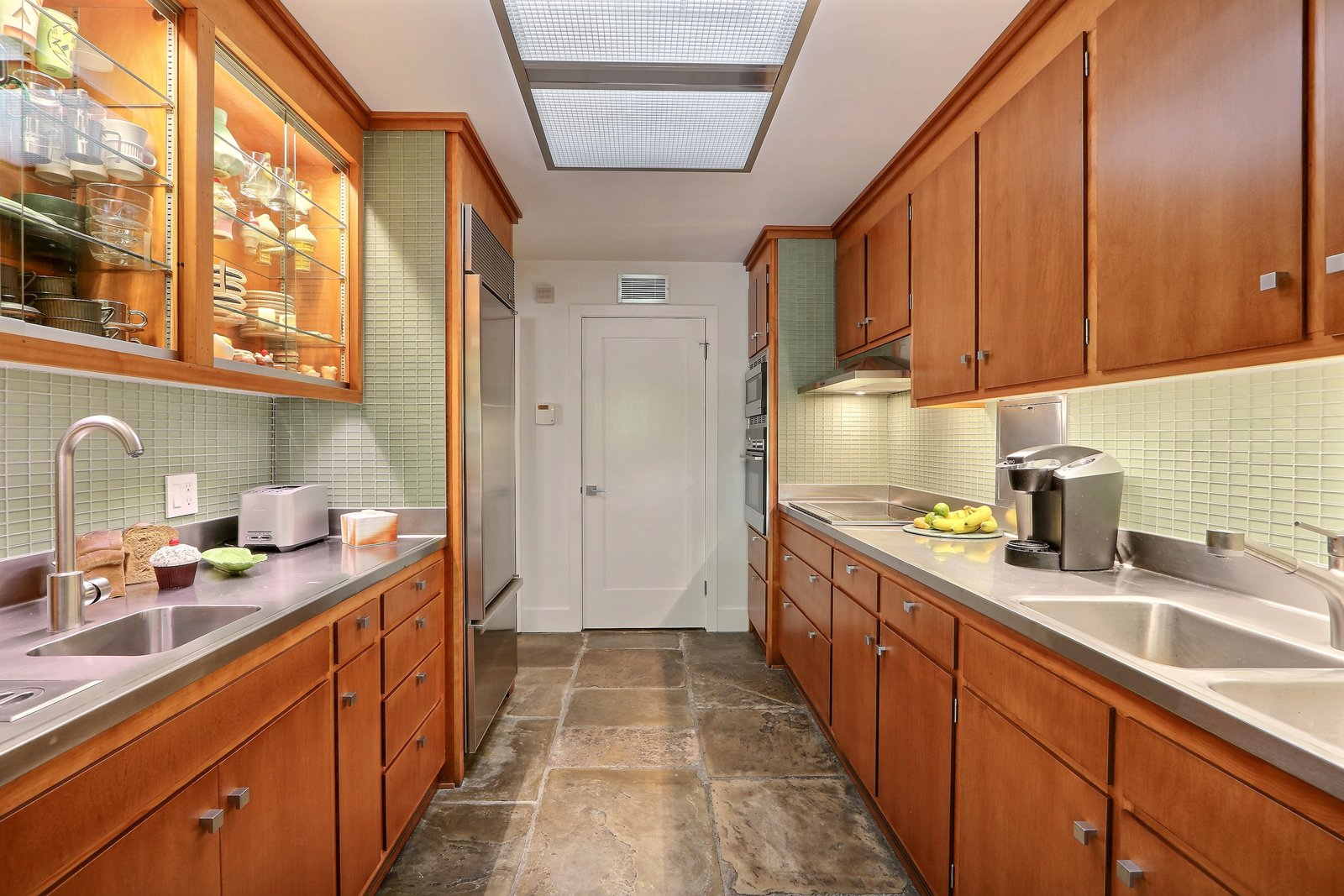 Kitchen, Refrigerator, Wall Oven, Cooktops, Range, Range Hood, Metal Counter, Wood Cabinet, Slate Floor, Glass Tile Backsplashe, and Ceiling Lighting The kitchen has been preserved and modernized with stainless steel Subzero, Fisher & Paykel appliances   The Hill Gowdy House
