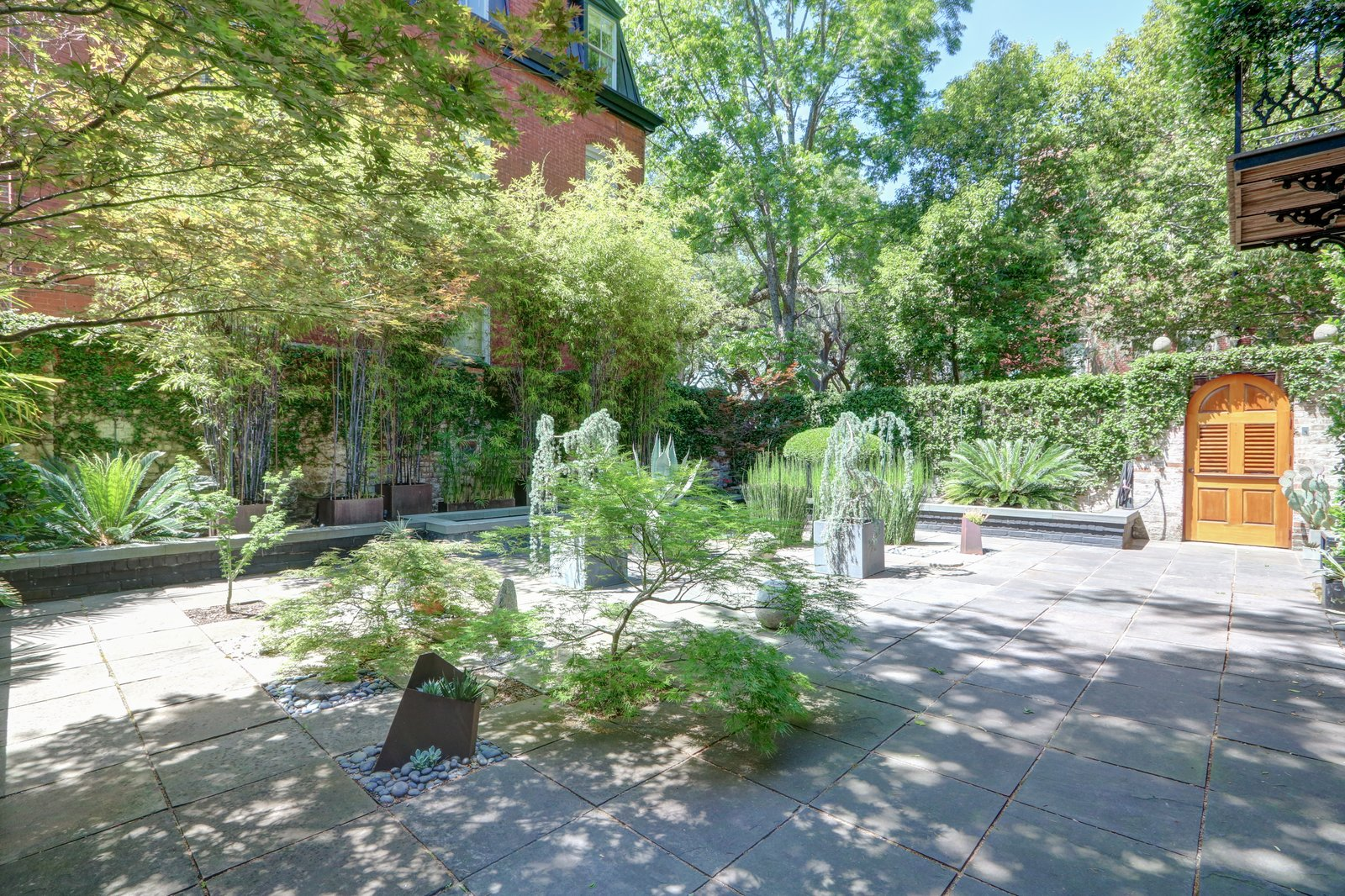 Outdoor, Side Yard, Trees, Hardscapes, Stone Patio, Porch, Deck, Pavers Patio, Porch, Deck, and Stone Fences, Wall Lush and private courtyard perfect for entertaining and relaxing  The Hill Gowdy House