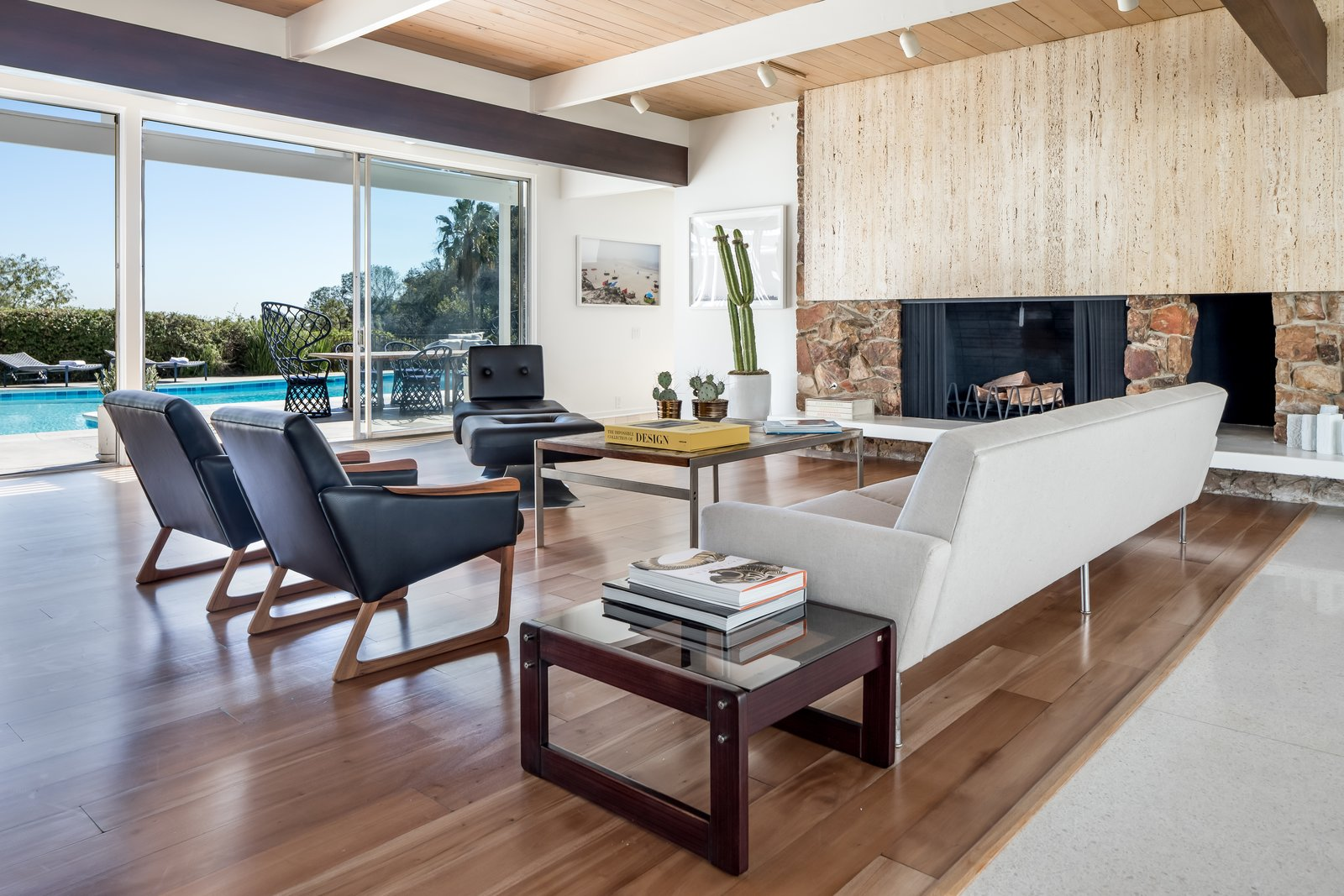 Living Room, End Tables, Sofa, Console Tables, Track Lighting, Light Hardwood Floor, Standard Layout Fireplace, and Wood Burning Fireplace A sandstone and travertine marble fireplace firmly anchors the entire living room while setting a warm and stylish tone to the house.   Best Photos