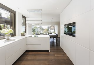 The all-white kitchen has an L-shaped work area and several cupboards. The work surfaces and cabinets are made of Corian, which gives the kitchen a soft elegance that blends beautifully with the oak parquet and the black steel wall. The highlight is the corner window seat.