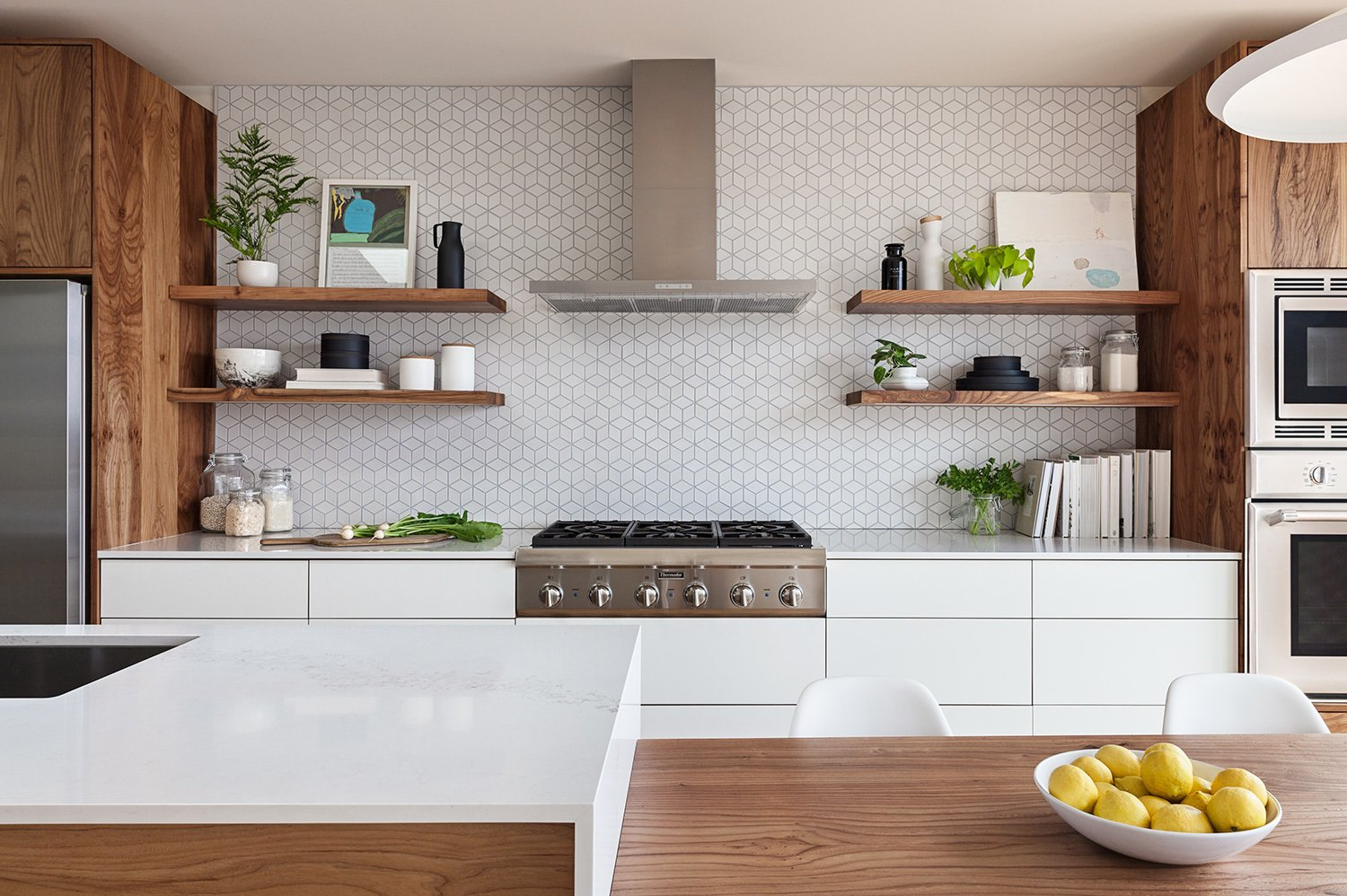 the heath ceramics wall tile backsplash was extended to full height and behind floating shelves to add texture and character to the minimal kitchen
