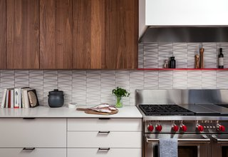 In a midcentury home renovation in California, HenryBuilt created the custom cabinetry in walnut and white laminate, and Heath Ceramics dimensional wall tiles give a nod to the home's modern architecture.