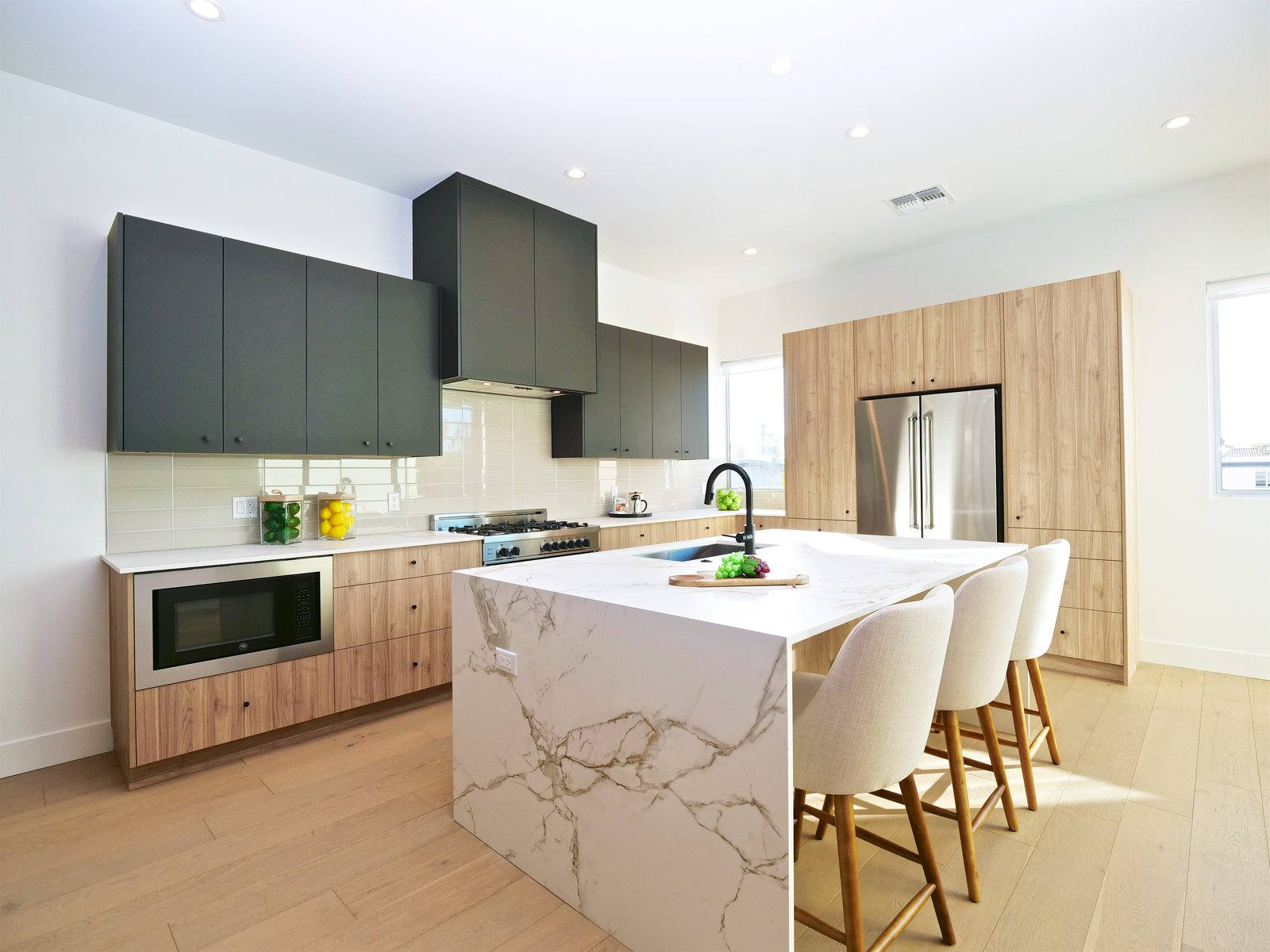 Kitchen, Medium Hardwood Floor, Ceiling Lighting, Refrigerator, Range, Microwave, Engineered Quartz Counter, Wood Cabinet, Undermount Sink, and Dishwasher Silestone Dekton countertops, a waterfall island and Bertazzoni appliance package.   Stacks Modern
