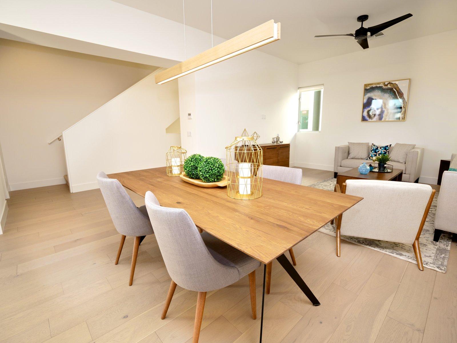 Dining Room, Table, and Medium Hardwood Floor Open floor plan concept with wood flooring and modern fixtures.  Stacks Modern