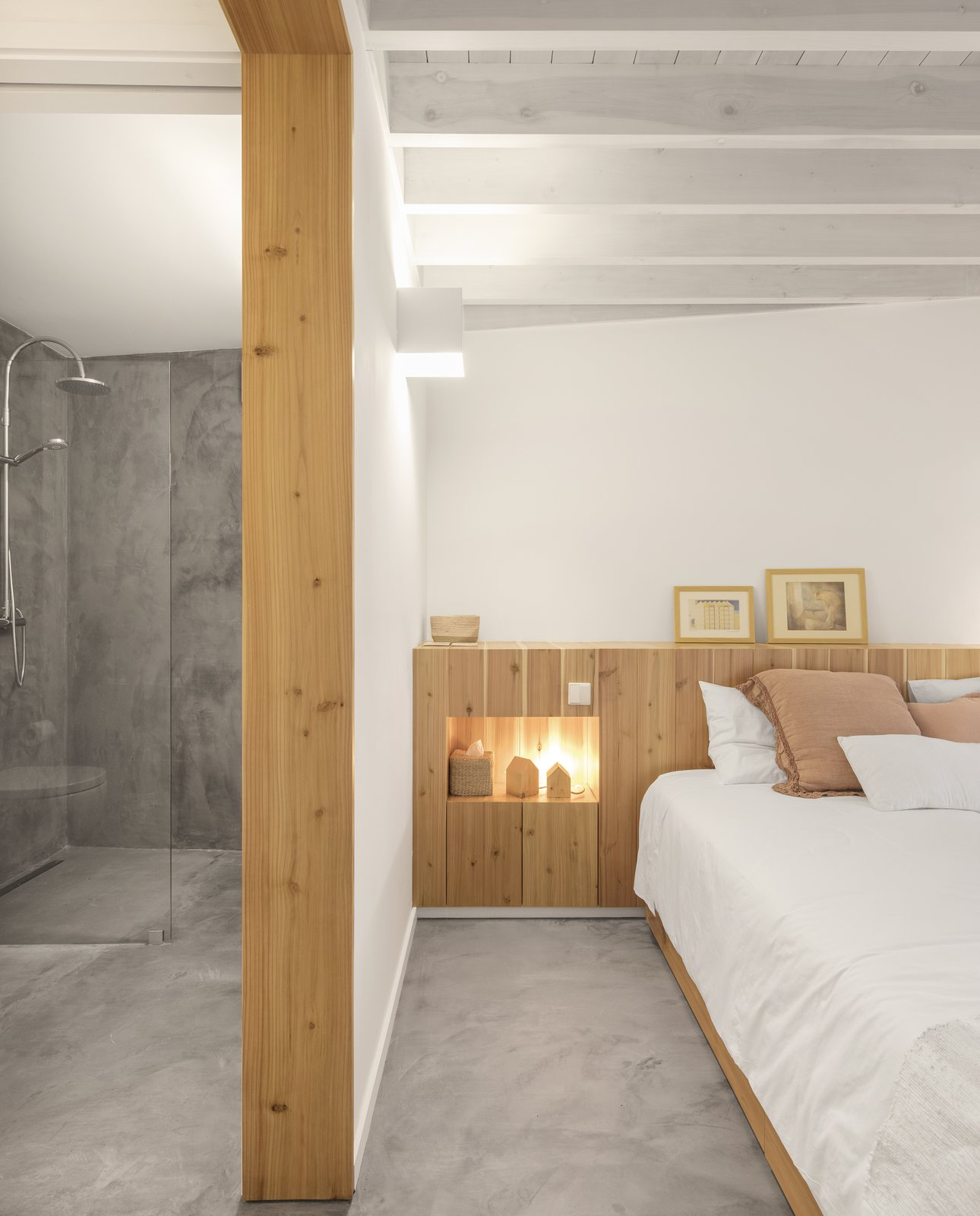 bedroom with small wood house shaped lamps in an inset wood bedside shelf