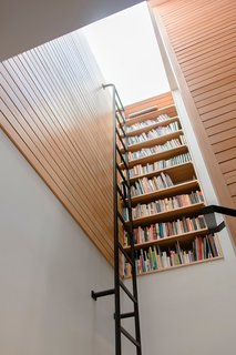 Vertical bookcase at stair landing