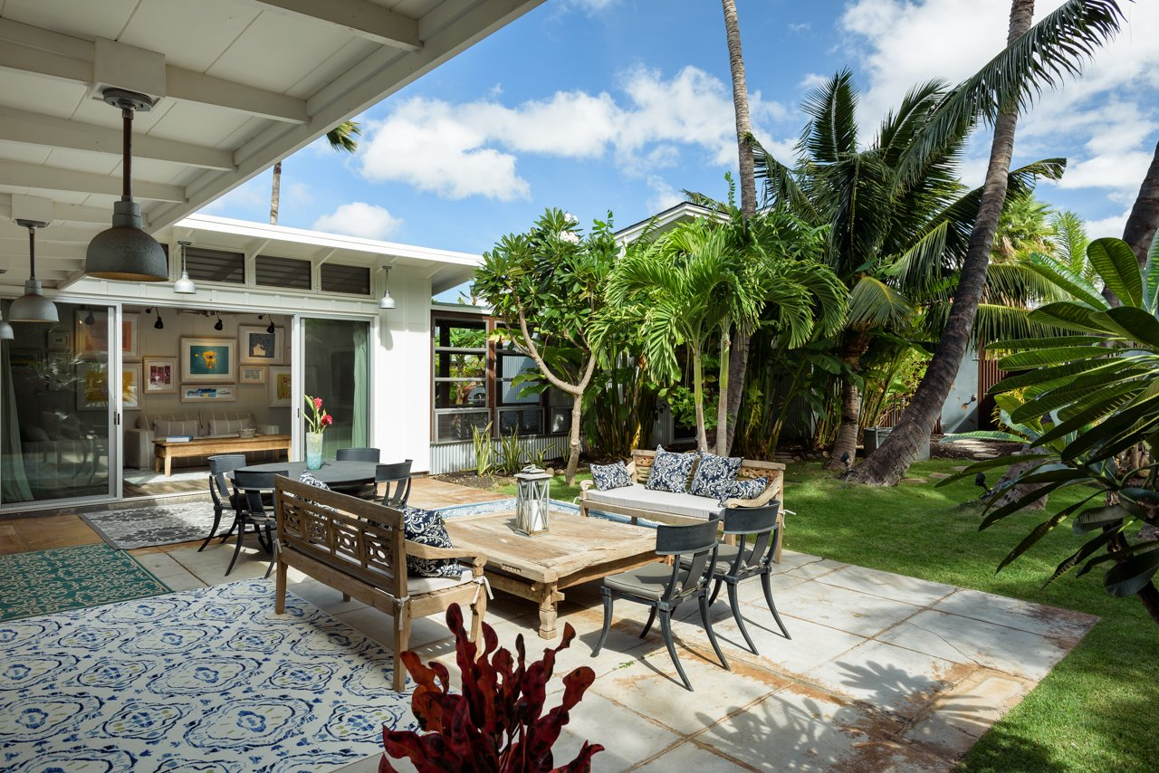 Outdoor, Back Yard, Trees, Flowers, Gardens, Walkways, Grass, Shower Pools, Tubs, Shower, Large Patio, Porch, Deck, Pavers Patio, Porch, Deck, Metal Fences, Wall, Hanging Lighting, and Landscape Lighting Courtyard combines indoor/outdoor living spaces  A Modern 1954 Plantation Style Home on Maui