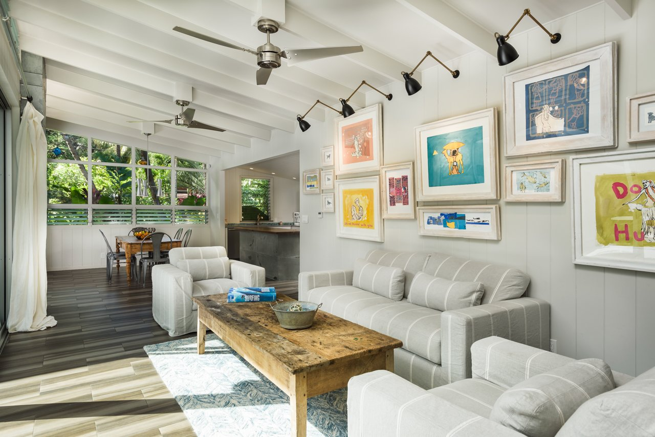 Living Room, Sofa, Coffee Tables, Wall Lighting, and Porcelain Tile Floor Main house living room with garden views to courtyard  A Modern 1954 Plantation Style Home on Maui