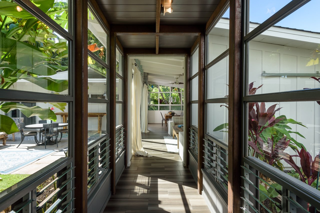 Hallway and Porcelain Tile Floor glass atrium walkway between master suite and living room.  A Modern 1954 Plantation Style Home on Maui