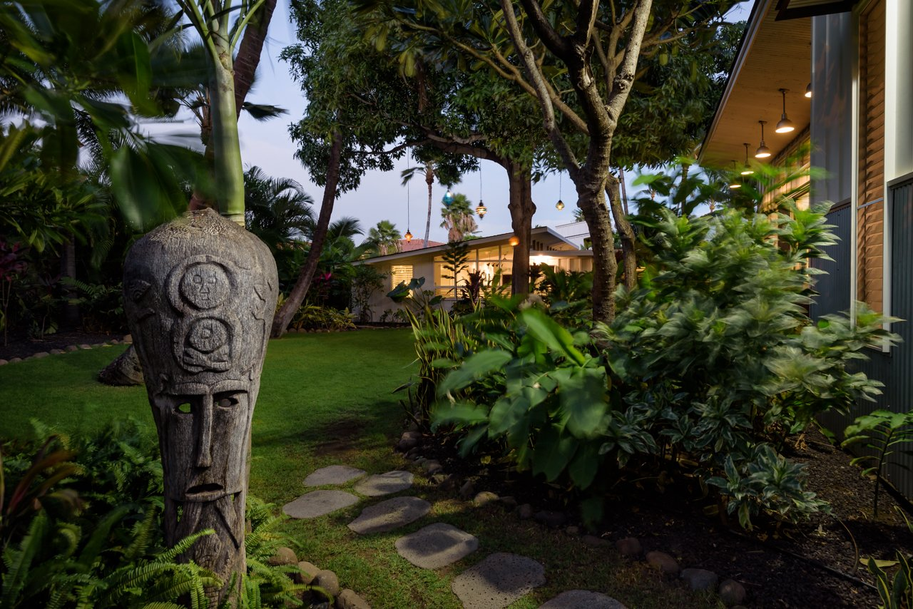 Outdoor, Front Yard, Trees, Shrubs, Grass, Gardens, Flowers, Walkways, Stone Fences, Wall, Landscape Lighting, and Hanging Lighting Front entrance with Tahitian statue and volcano rock pavers  A Modern 1954 Plantation Style Home on Maui