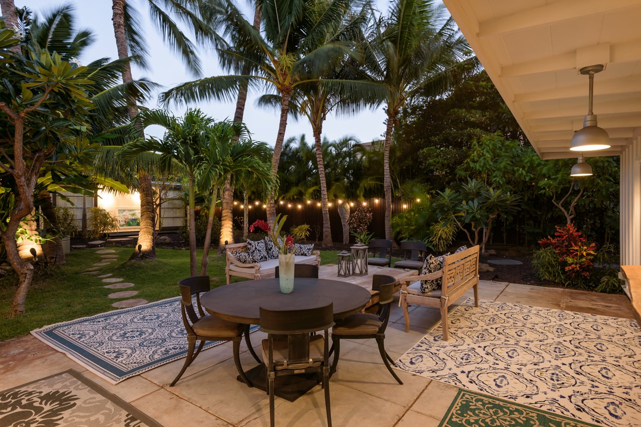 Outdoor, Back Yard, Garden, Trees, Flowers, Shrubs, Grass, Gardens, Walkways, Large Patio, Porch, Deck, Concrete Patio, Porch, Deck, Metal Fences, Wall, Hanging Lighting, and Landscape Lighting Courtyard in the evening  A Modern 1954 Plantation Style Home on Maui
