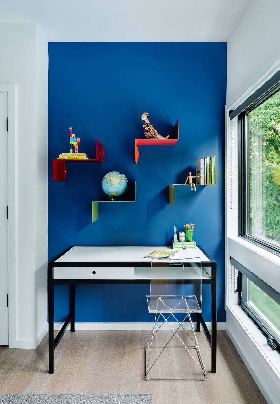 Bedroom, Bookcase, Storage, Chair, Ceiling, Light Hardwood, and Shelves A pop of color, and a window to reflect out to in the son's bedroom.  Best Bedroom Ceiling Shelves Bookcase Photos from Roslyn Road Residence