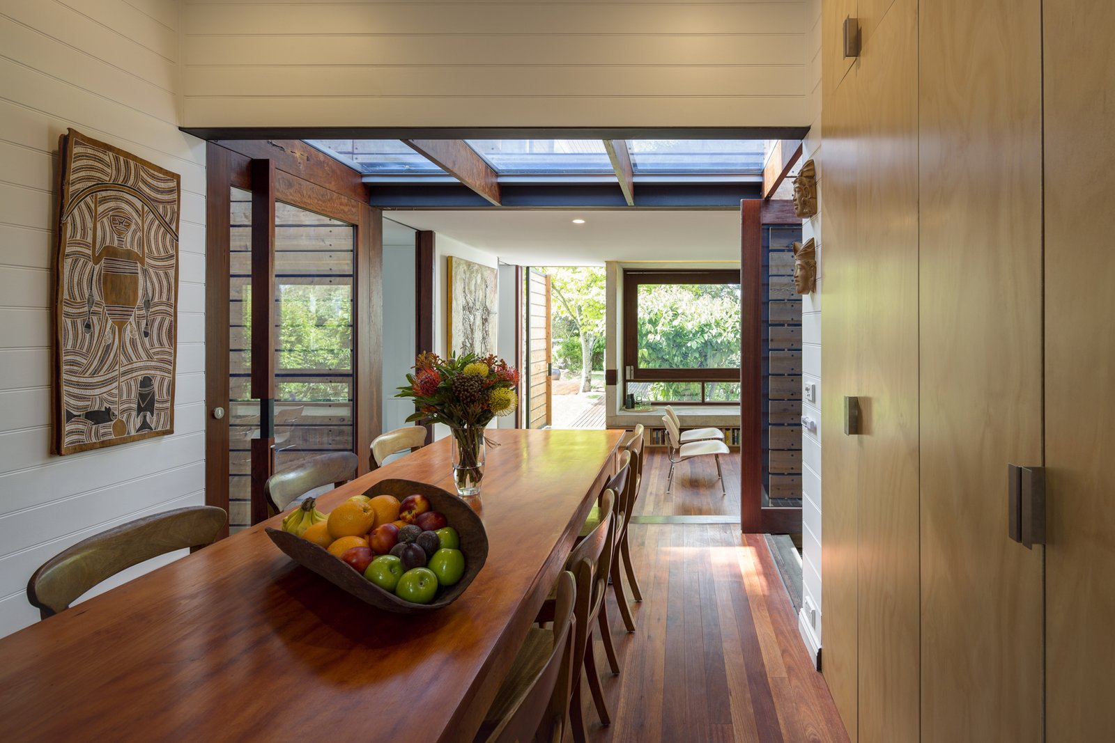 Dining Room, Table, Storage, and Medium Hardwood Floor Shifting volumes of living spaces  linked by restored industrial work bench.  Kihilla by James Thomas Barclay