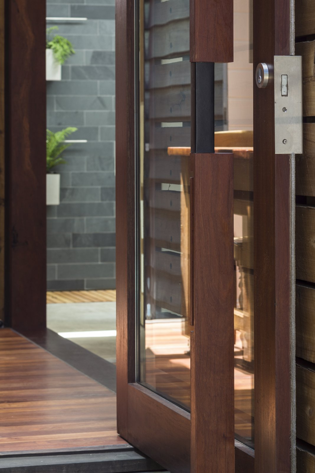 Doors, Exterior, Swing Door Type, and Wood Custom pivot door; composition of river red gum, kangaroo leather, stainless steel, and glass.  Kihilla by James Thomas Barclay