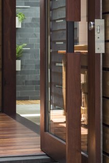 Custom pivot door; composition of river red gum, kangaroo leather, stainless steel, and glass.