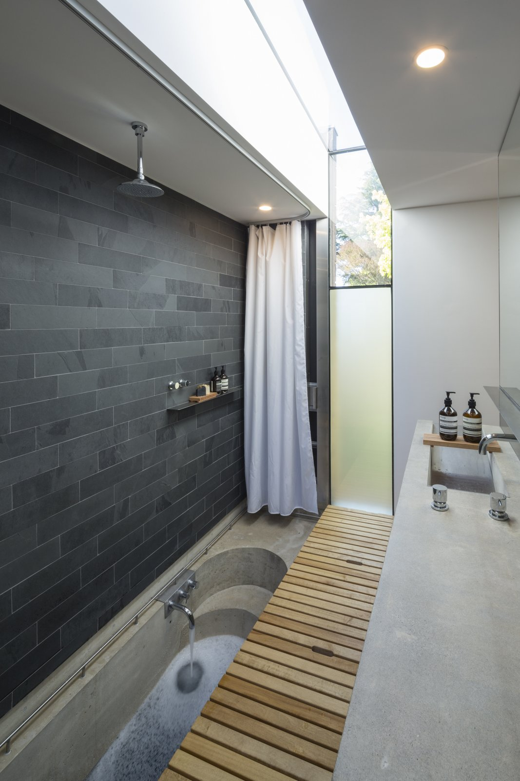 Bath, Concrete, Metal, Light Hardwood, Concrete, Open, Ceiling, Stone Tile, and Metal Off form concrete bath hidden below timber trapdoor.  Best Bath Open Light Hardwood Photos from Kihilla