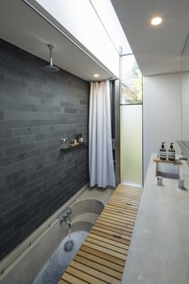 Off form concrete bath hidden below timber trapdoor.