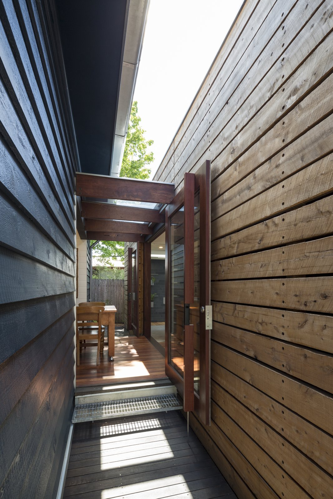 Doors, Wood, Exterior, and Swing Door Type Custom pivot doors off dining room between new and existing.  Kihilla by James Thomas Barclay