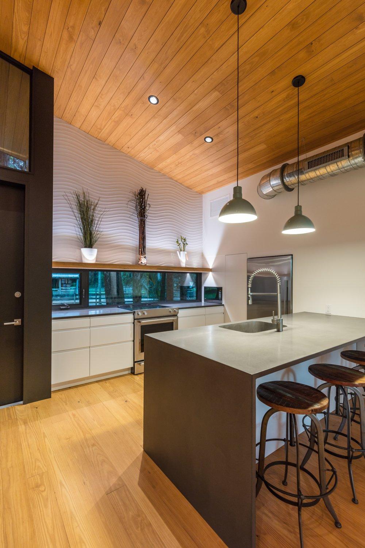 Kitchen, Refrigerator, Range, Microwave, White Cabinet, Medium Hardwood Floor, Pendant Lighting, Recessed Lighting, and Accent Lighting Eat-in Kitchen. Ikea cabinets. Concrete counters.  Mike's Hammock by Josh Wynne