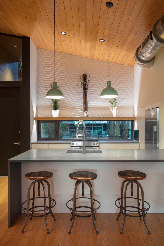 Kitchen, Refrigerator, Concrete Counter, Range, Medium Hardwood Floor, Pendant Lighting, Recessed Lighting, Accent Lighting, and White Cabinet Eat-in Kitchen  Mike's Hammock by Josh Wynne