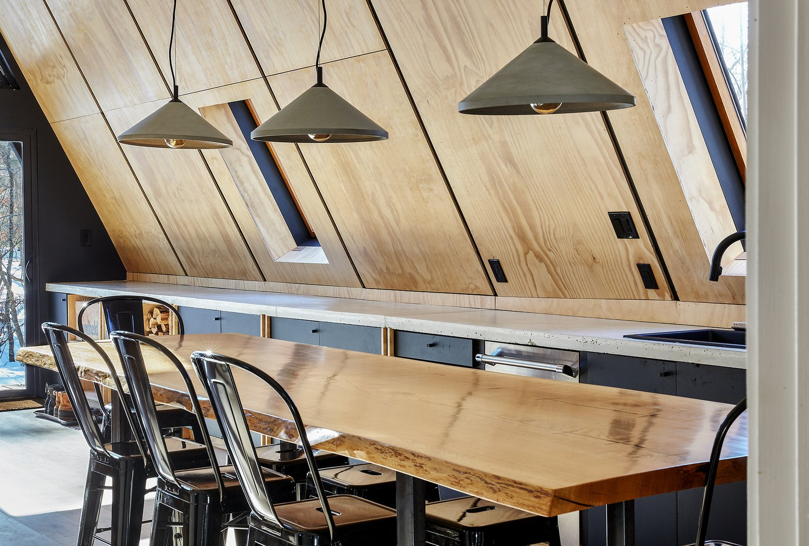 Kitchen, Light Hardwood Floor, Wood Cabinet, Dishwasher, Drop In Sink, Pendant Lighting, and Concrete Counter Live edge dining table / kitchen island by Timberforge Woodworks  Lokal A-Frame