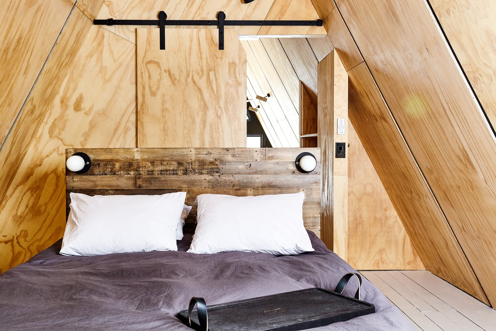 Bedroom, Bed, Painted Wood Floor, and Accent Lighting Pine plywood A-Frame interior and sliding barn door. Custom tray by Peg & Awl.  Lokal A-Frame