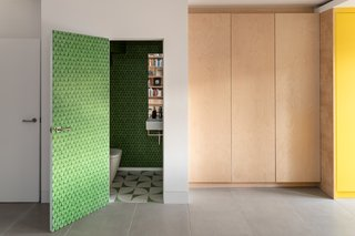 A bright green, patterned wallpaper envelops the bathroom on the lower level.