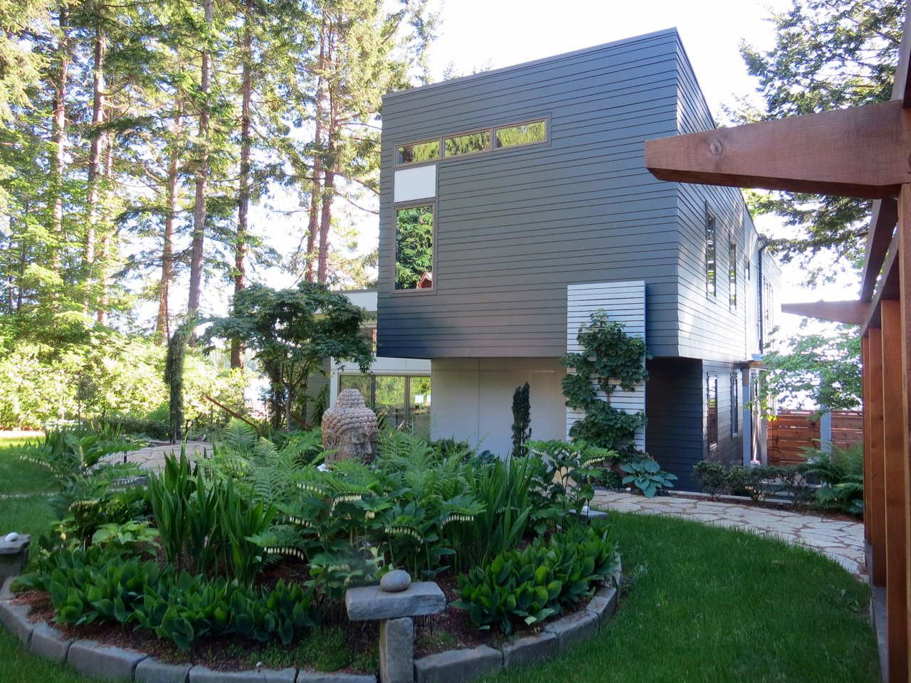 Outdoor, Back Yard, Trees, Grass, Hardscapes, Walkways, Gardens, Shrubs, and Wood Fences, Wall Back yard upon entry  Cortes Island Custom Blu Prefab by Mark Spevakow