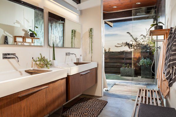 The master bath of Highlands Ranch features twin Duravit cabinets with concrete sinks, all lit from above by an automated skylight. SGS' design provides passive cooling when coupled with the garden-level windows. The ocean view shower provides a seamless indoor/outdoor bathing experience.