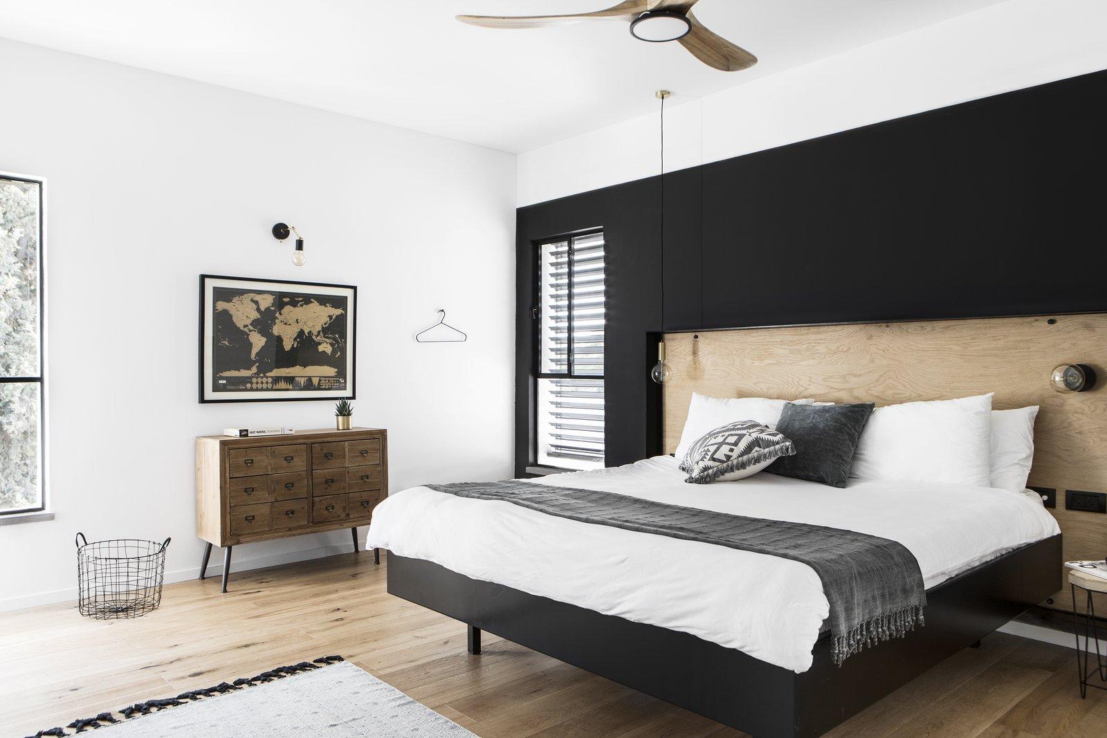 Bedroom, Bed, Dresser, Wall Lighting, Pendant Lighting, and Medium Hardwood Floor The master bedroom.  Nir Am House by Shir Shtaigman
