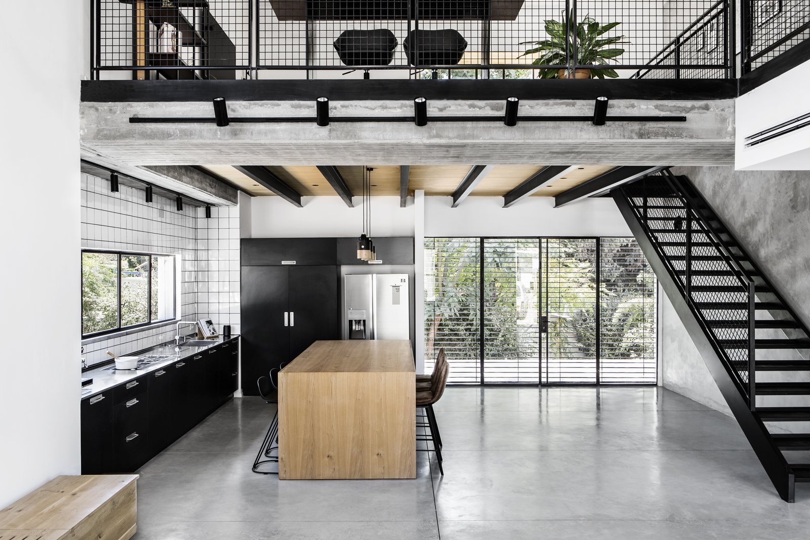 Kitchen, Refrigerator, Cooktops, Metal Counter, Colorful Cabinet, Concrete Floor, Ceramic Tile Backsplashe, Ceiling Lighting, and Undermount Sink Both floors.   Nir Am House by Shir Shtaigman