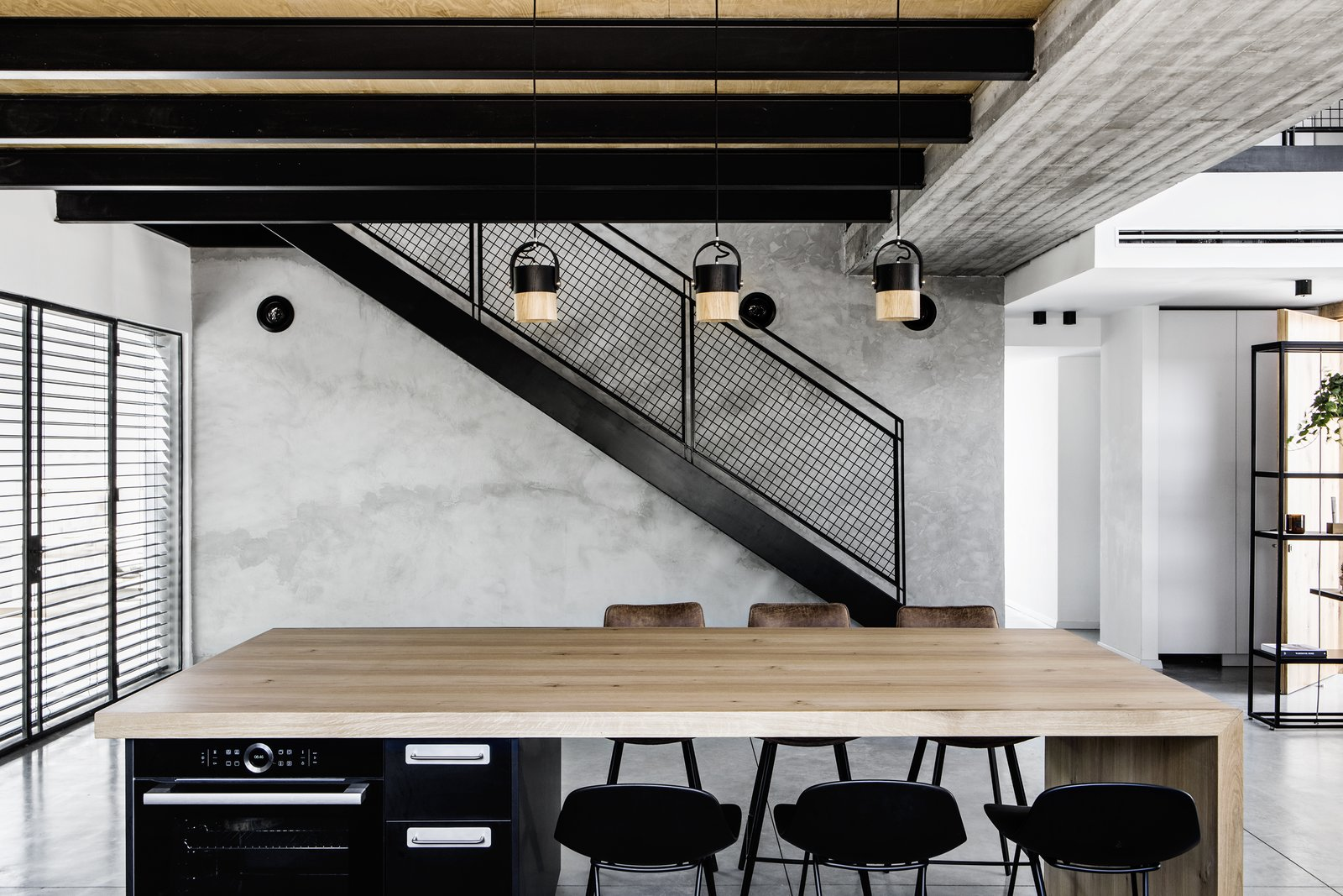 Dining Room, Bar, Stools, Ceiling Lighting, Pendant Lighting, and Concrete Floor Metal staircase on concrete wall. Hand made lighting fixtures by Asaf Weinbroom.   Nir Am House by Shir Shtaigman