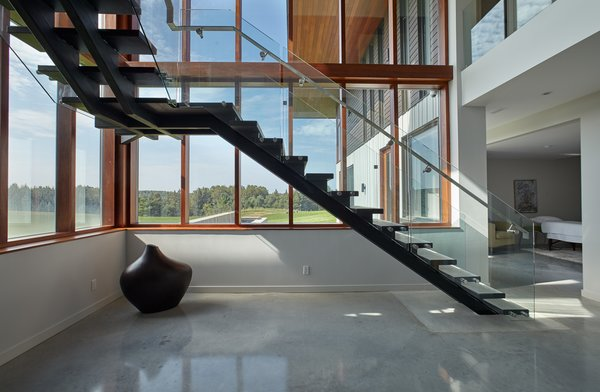 Sleek concrete tread stair meets polished concrete flooring on lower level