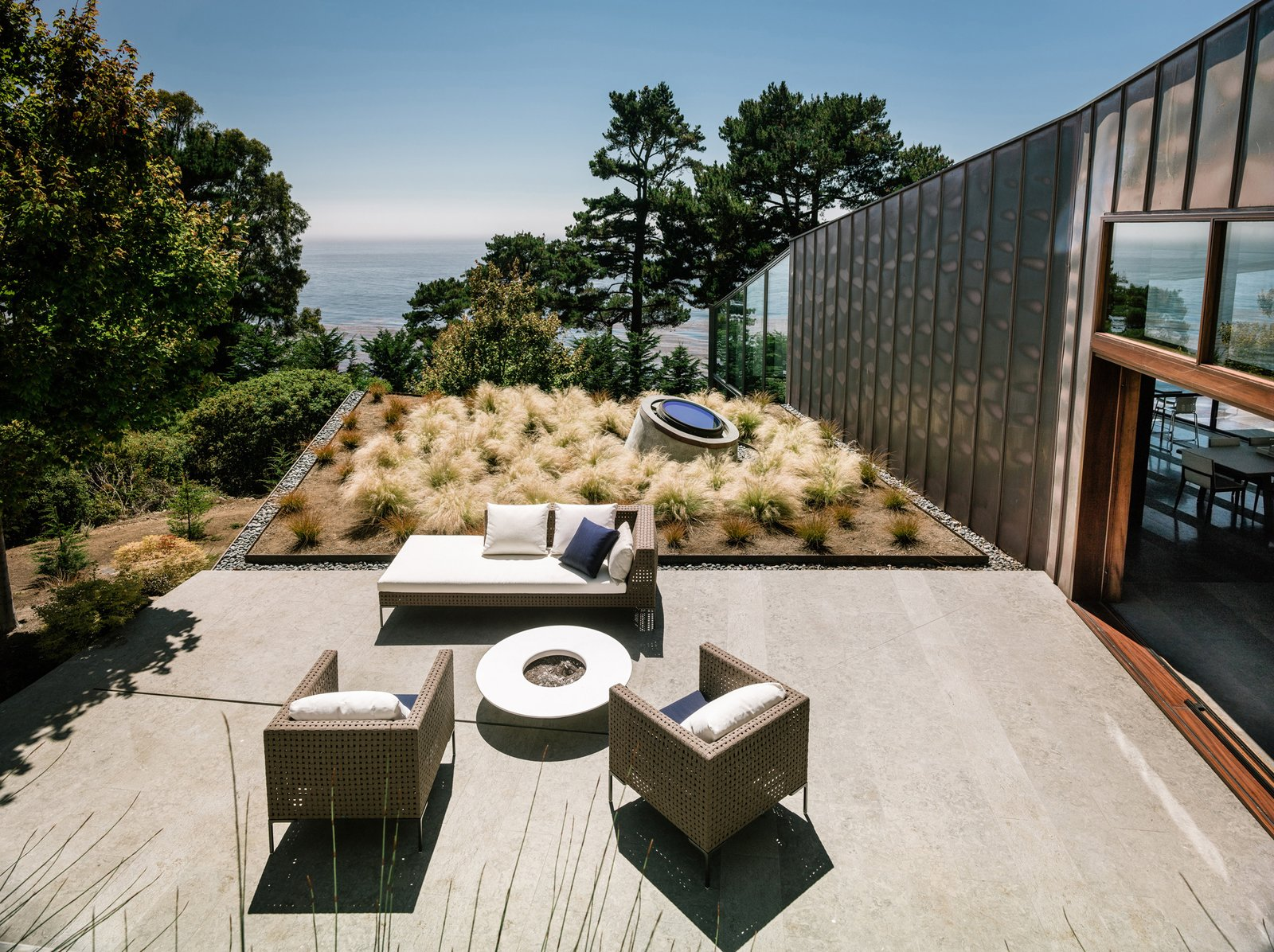 "Outdoor, Side Yard, Trees, Shrubs, Stone Patio, Porch, Deck, Landscape Lighting, Grass, Rooftop, and Concrete Patio, Porch, Deck ""The house's two main façades express both shelter and exposure. On the north, clear expanses of glass reveal ocean and coastline views; long strips of translucent channel glass dapple the light, playing on the sea's shimmering surface. The south façade, clad in copper, which wraps over the roof, is mostly enclosed, offering a retreat from the forces of nature. Roof overhangs on the east and west protect the windows and the front door from the harshness of sun and wind,  Photo 2 of 19 in 18 Modern Fireplaces and Fire Pits to Inspire Outdoor Living from Fall House"