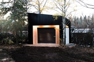 "While the idea of a motorcycle shed might not initially scream ""elegant she shed,"" there's a lot to love in this shed by Drop Structures. The exterior lighting gives the building a presence at night, and the mixing of natural wood, a white door, and darker cladding make for simple but modern exterior."